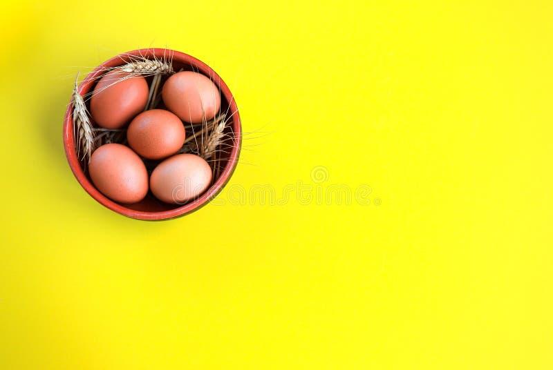 Ovos orgânicos de Brown em uma placa redonda cerâmica com as orelhas do trigo em um fundo amarelo, conceito da Páscoa foto de stock