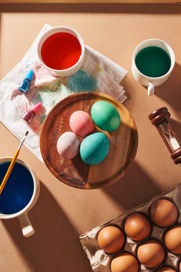 Ovos, pinturas coloridas, escovas, lápis em um fundo de madeira, ovos colorindo, preparando-se para a Páscoa, feriado sazonal da  fotografia de stock royalty free