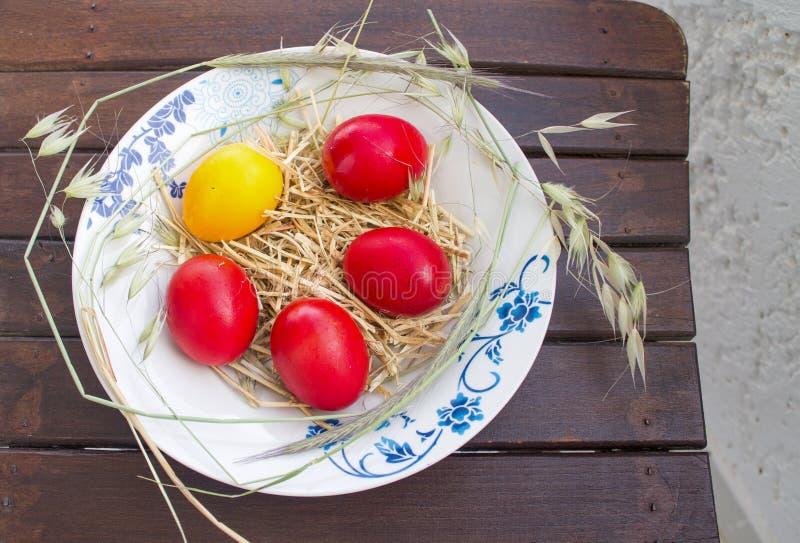 Ovos vermelhos e amarelos da Páscoa com feno na placa fora imagens de stock royalty free