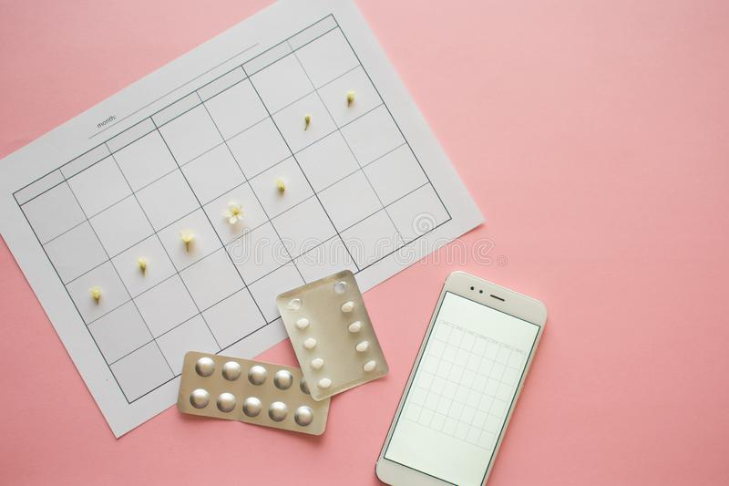 Ovulation cycle, concept. Calendar for a month, flowers indicate. The days of possible conception. Birth control pills, contraceptives royalty free stock photography