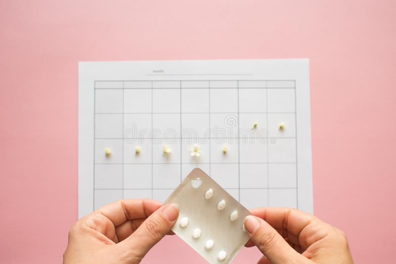 Ovulation cycle, concept. Calendar for a month, flowers indicate. The days of possible conception. Birth control pills, contraceptives stock image