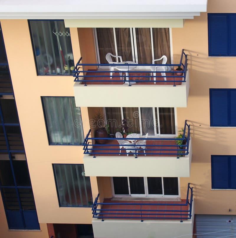 Ow балконов с таблицами и стульев в оранжевом и голубом конкретном жилом доме стоковые изображения