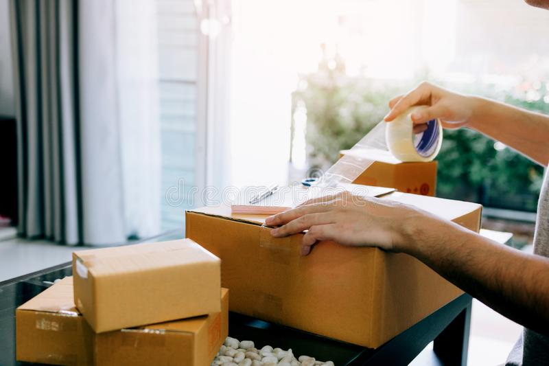 Owener novo asiático do adolescente do produto de embalagem da empresa de pequeno porte em umas caixas que preparam o para a entr imagem de stock