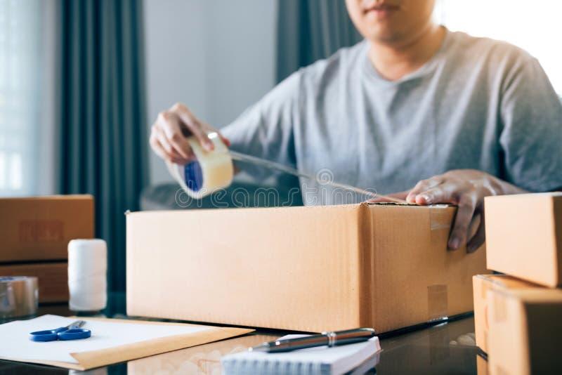 Owener novo asiático do adolescente do produto de embalagem da empresa de pequeno porte em umas caixas que preparam o para a entr imagens de stock