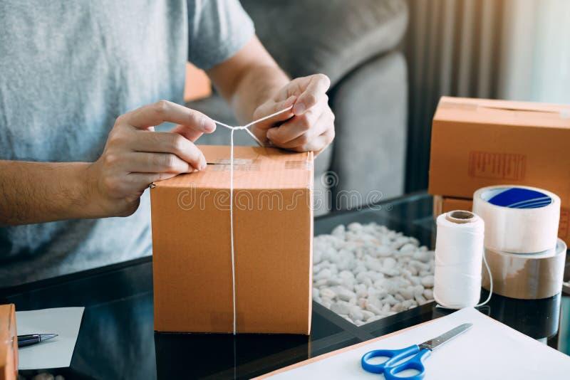 Owener novo asi?tico do adolescente do produto de embalagem da empresa de pequeno porte em umas caixas que preparam o para a entr foto de stock