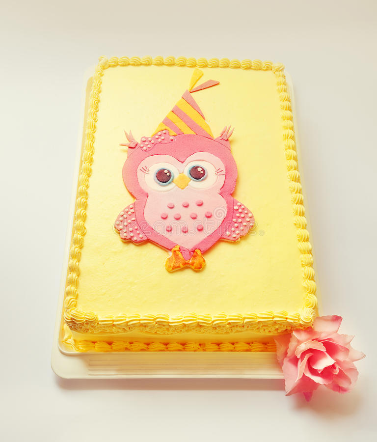 Owl Birthday Cake. Yellow birthday cake with pink owl of sugar on the top stock photography