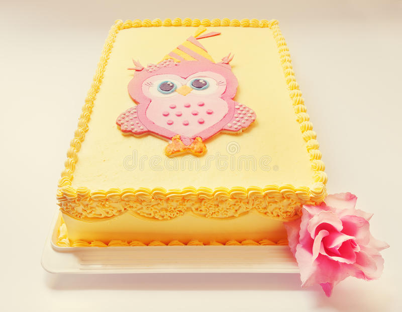 Owl Birthday Cake. Yellow birthday cake with pink owl of sugar on the top royalty free stock image