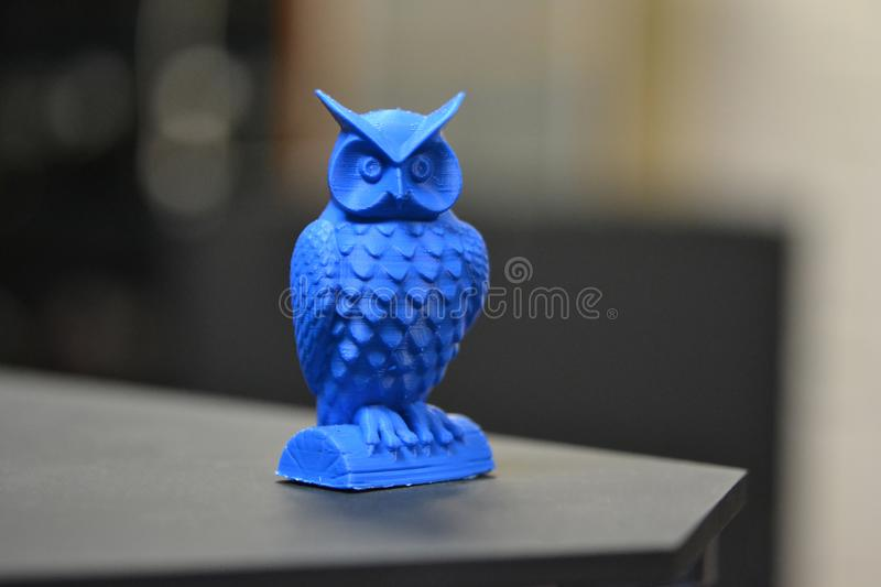 An owl made on a 3d printer stands on a blurry dark background. Close-up. Progressive modern additive technologies 4.0 industrial revolution royalty free stock photo
