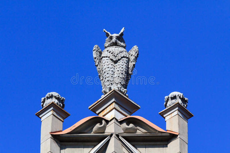 Owl sculpture. A stone owl sculpture on the top of a building on clear blue sky in St. Petersburg, Russia stock image