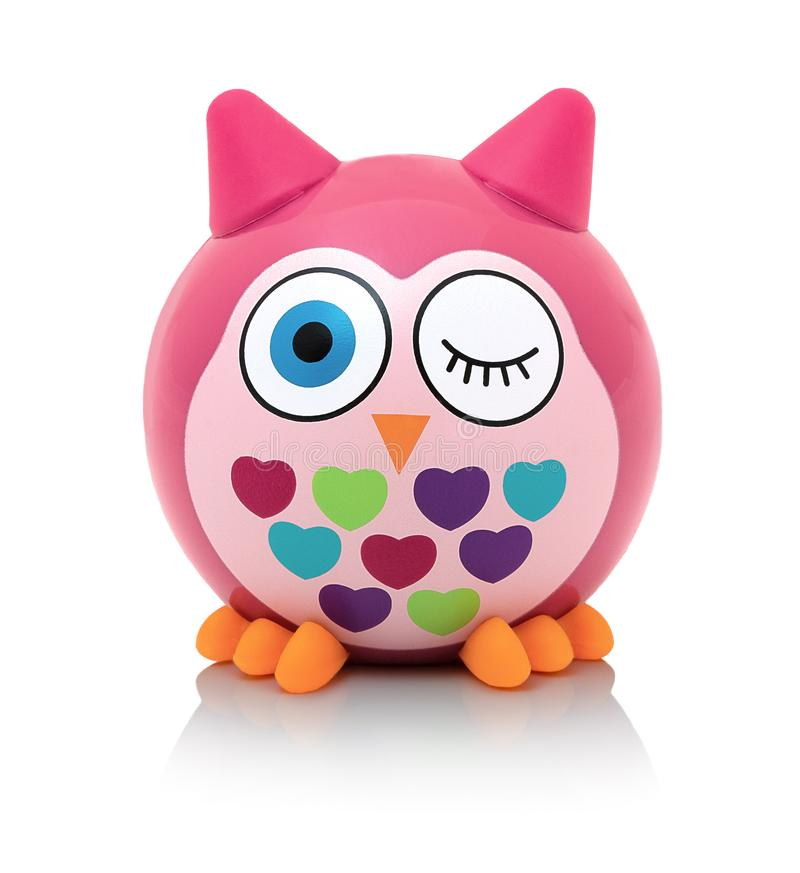 Owl toy on white background with shadow reflection. Owl the bird of prey on white backdrop. Rainbow colored plastic toy. stock photo