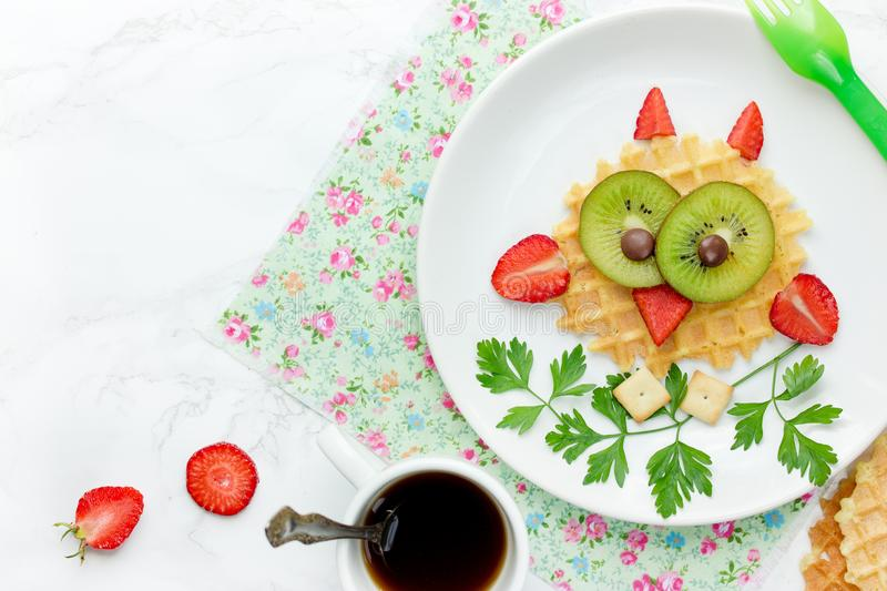 Owl waffle - funny healthy breakfast dessert snack idea for kids. Sweet dutch waffles with strawberry and kiwi shaped cute owl royalty free stock image