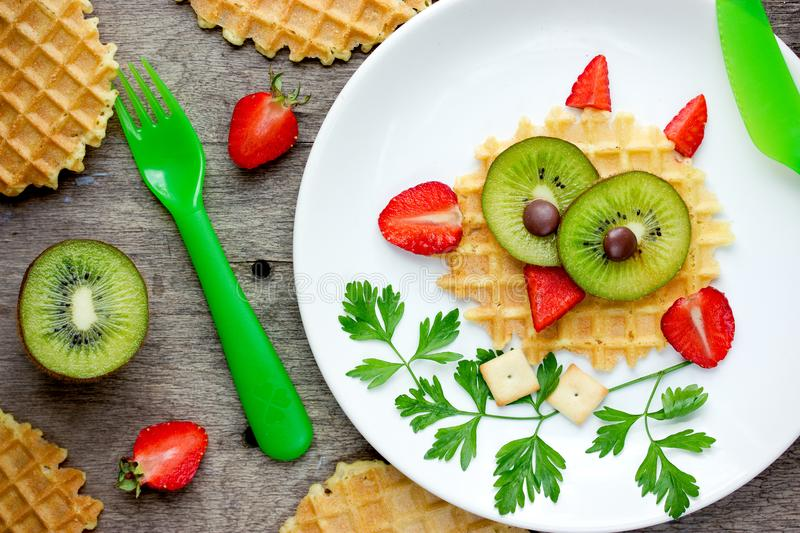 Owl waffle - funny healthy breakfast dessert snack idea for kids. Sweet dutch waffles with strawberry and kiwi shaped cute owl royalty free stock photos