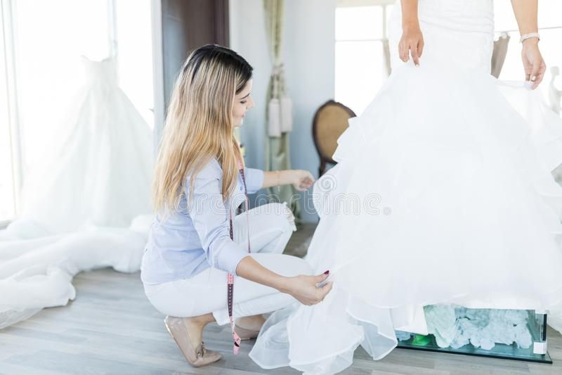 Owner Arranging Ruffles Of Bride`s Dress In Store stock images