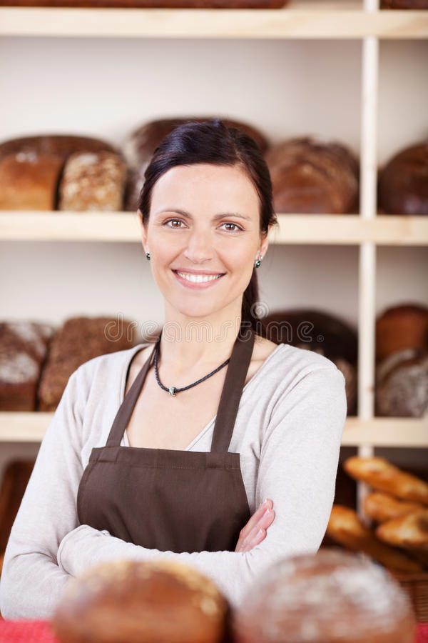 Owner of a bakery standing with folded arms. Attractive young female owner of a bakery standing with folded arms looking at the camera with a confident smile stock photography
