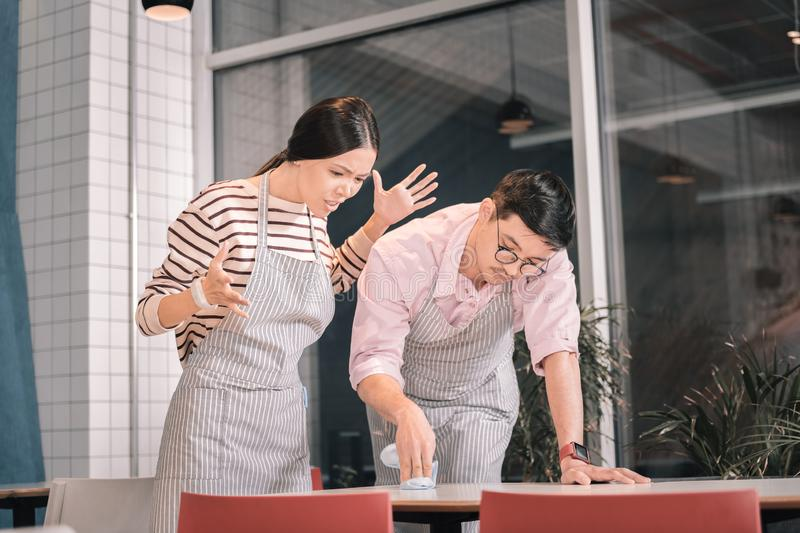 Owner of cafeteria feeling unsatisfied checking the cleanness of table. Checking the cleanness. Owner of little cafeteria feeling unsatisfied while checking the royalty free stock photos