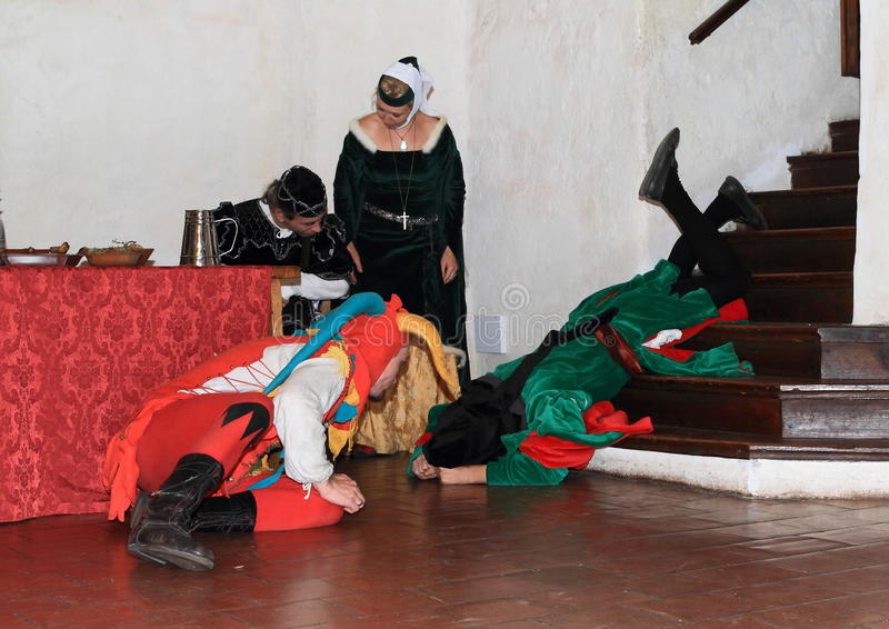 Owner of castle falling down from stairs. Jester in colorful costume watching owner of castle Puta falling down from stairs during Night performance A dozen royalty free stock image