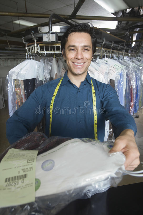 Owner Checking Clothes Tag In Laundry. Portrait of young male owner giving dry cleaned clothes at counter stock photos