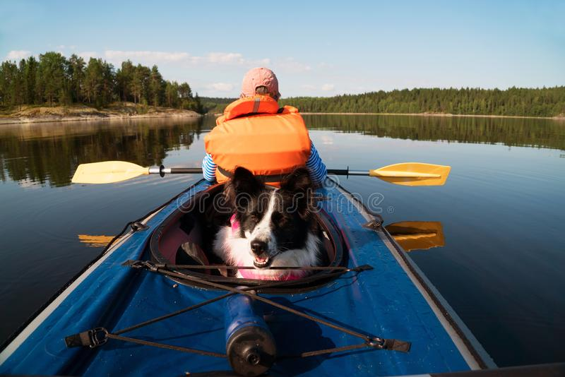 The owner and the dog in a life jacket floating in a kayak boat. Dog sitting in the boat .lake Ladoga.Karelia,Skerries royalty free stock photos