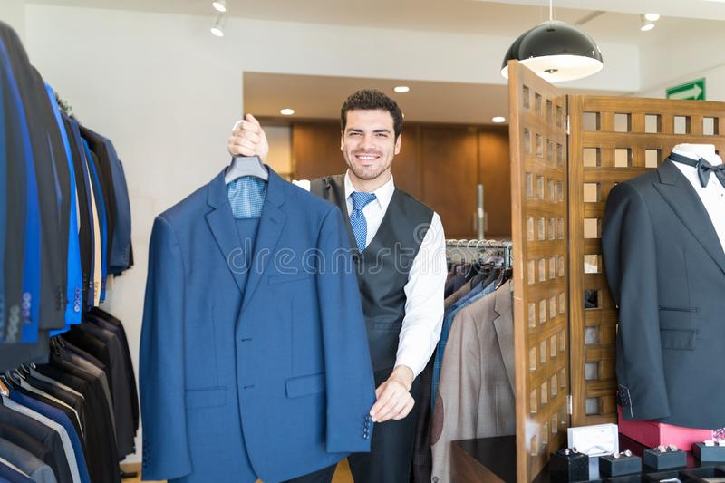 Owner Holding Blue Blazer In His Rental Shop. Smiling young tailor showing men`s party wear on rent for all occasions at store royalty free stock images