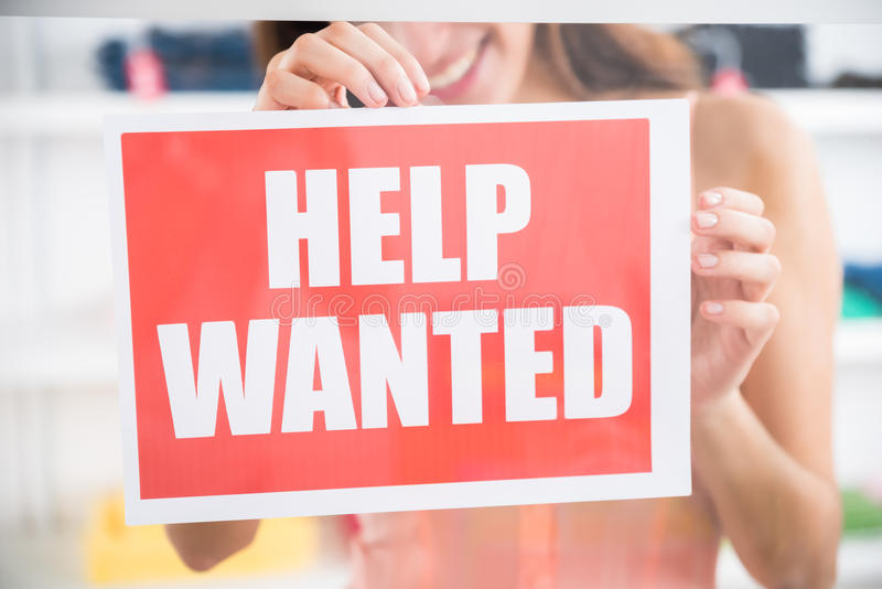 Owner Holding Help Wanted Sign In Retail Store. Midsection of smiling female owner holding help wanted sign in retail store stock photos