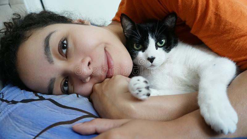 Owner and pet lie on the bed. Cat owner is lying down and hugging with the pet royalty free stock image