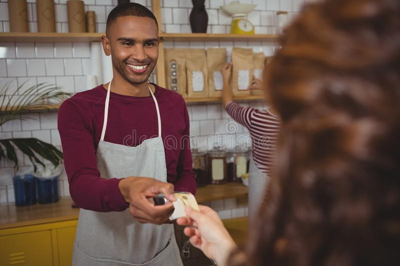 Owner receiving payment from customer in cafe royalty free stock photography