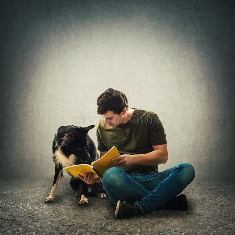 Owner seated on floor training his cute puppy reading together an interesting book stock images