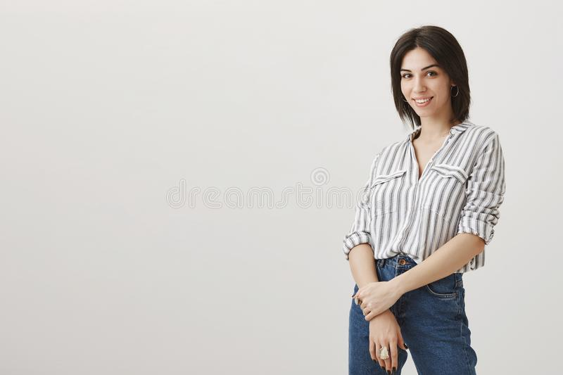 Owner of shop greets new customers. Portrait of successful attractive female entrepreneur standing half-turned over gray royalty free stock image