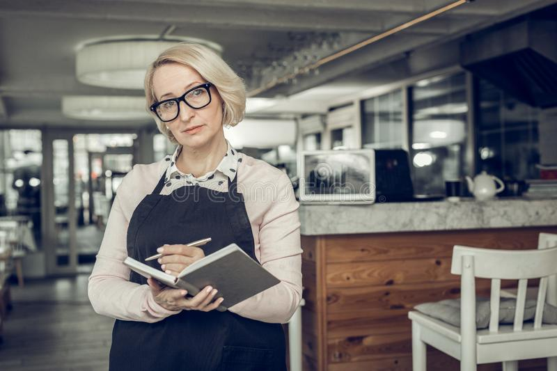 Smart successful businesswoman wearing glasses owning restaurant stock image