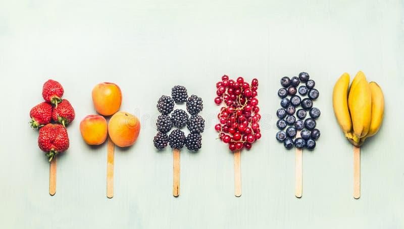 Owoc i jagody dobierali popsicles na lekkim turkusowym tle, odgórny widok zdrowa żywność zdjęcia stock