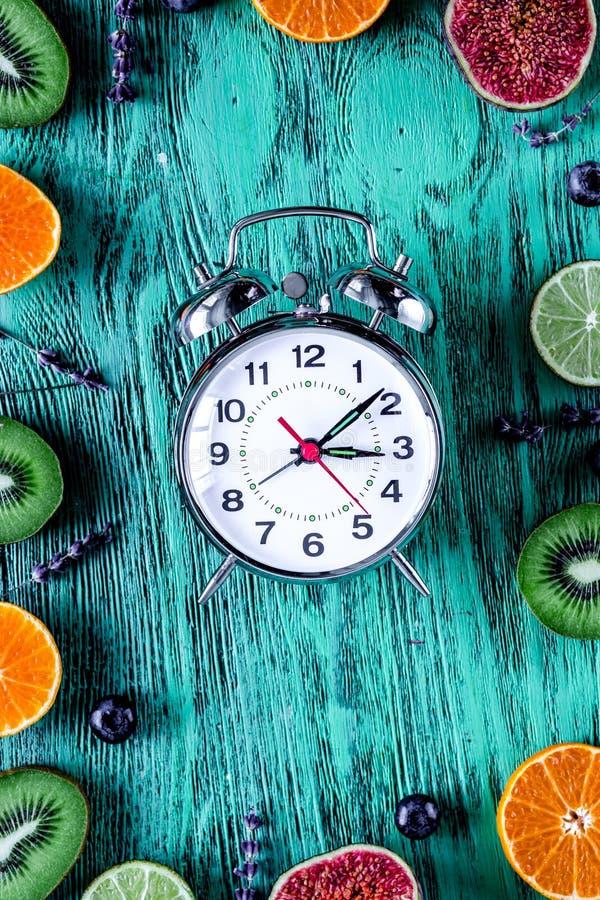 Owoc, lawenda, czarna jagoda egzamin próbny z zegarem na błękitnym biurka backg zdjęcie stock