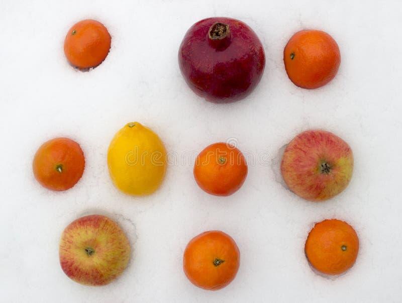 Owoc na śniegu, Tangerine, cytryna, Apple, granatowa tło obraz royalty free