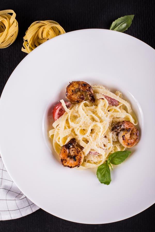 Owoce morza łuskanie Makaron z piec na grillu krewetek garnelami z pomidorami, świeżymi ziele basile i pikantność, obraz stock