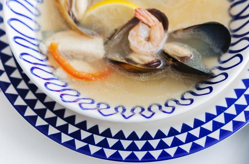 Owoce morza polewka z mussels, krewetki, ryba na białym talerzu z błękitnym ornamentem w restauracji fotografia royalty free