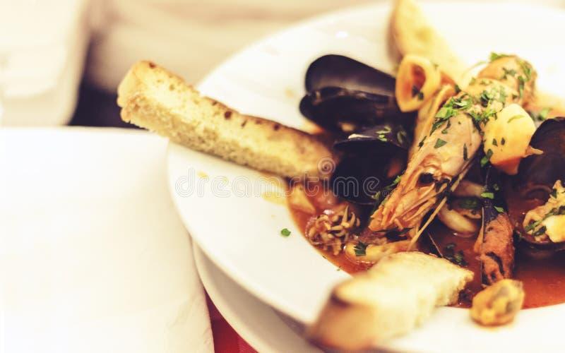 Owoce morza polewka z mussels, krewetki, ryba na białym talerzu z błękitnym ornamentem w restauracji Taormina, Sicily, Włochy obraz royalty free