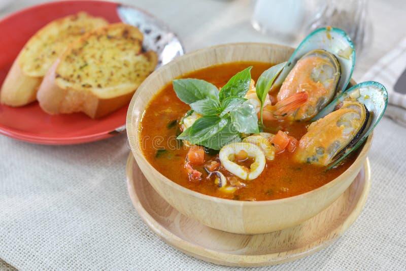 Owoce morza pomidorowa polewka słuzyć z czosnku chlebem na tnącej desce obraz royalty free
