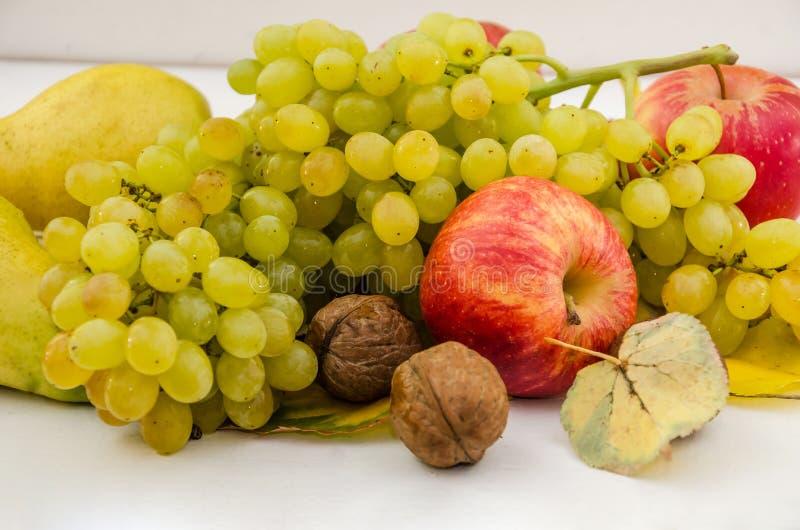 Owoce na białym Jabłka, gruszki i winogrona Zbliżenie Pięknie ułożone owoce na stole zdjęcia royalty free