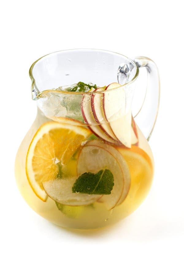 Owocowa lemoniada z plasterkami jab?ka i pomara?cze w dzbanku na odosobnionym bia?ym tle fotografia stock