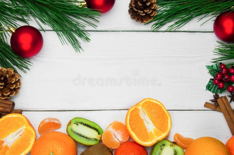 Owocowa pomarańcze, tangerine i kiwifruit, Gałęziasta choinka i czerwieni piłka z kijami na białych drewnianych roczników półdupk obraz stock