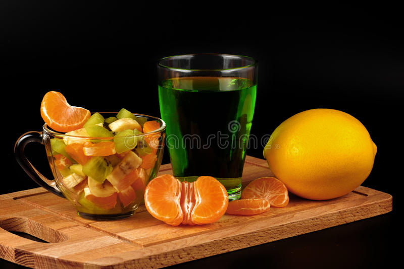 Owocowa sałatka, cytryna, segmenty tangerine i szkło z napojem, obraz stock