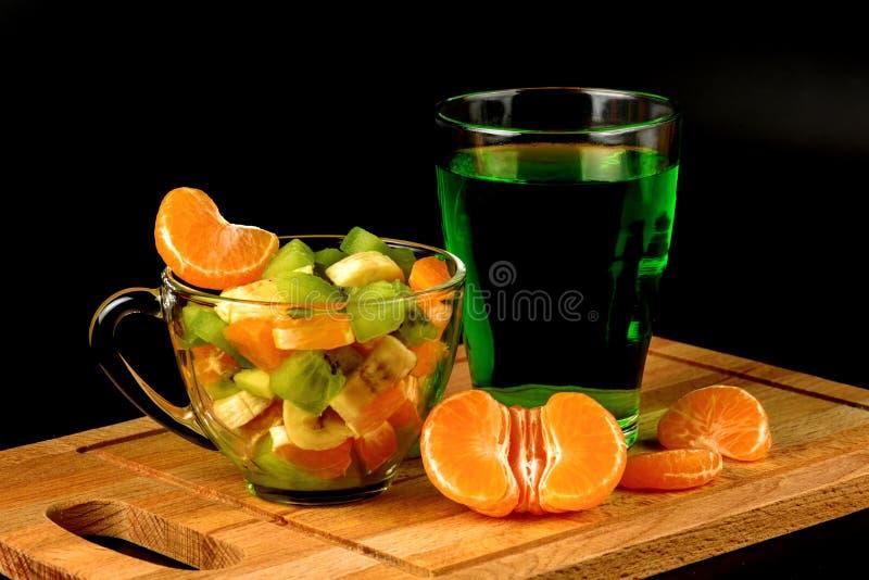 Owocowa sałatka, segmenty tangerine i szkło z napojem, obrazy stock