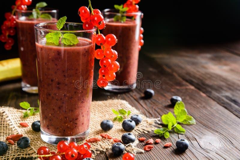Owocowi smoothies z czerwonymi rodzynkami, czarną jagodą, bananem, goji jagodami i chia ziarnami, obrazy royalty free