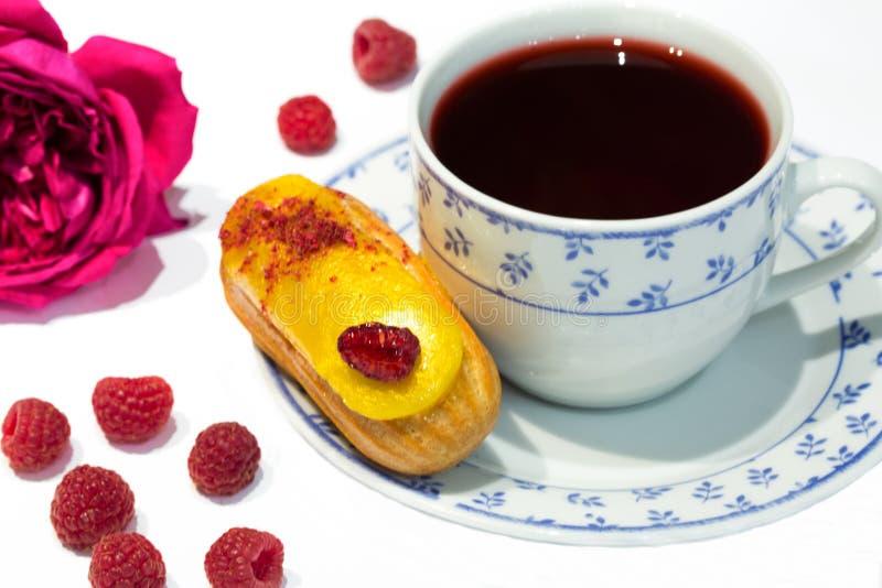 Owocowy żółty eclair tort z poślubnika Sudan herbacianą różaną herbatą, se obraz stock