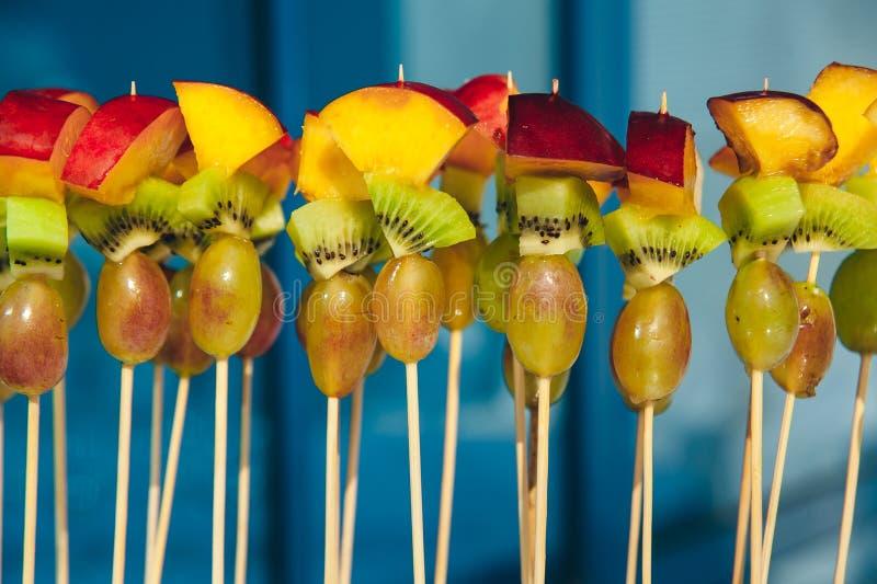 Owocowy jarski canape przy skewers z winogronami, kiwi i brzoskwinią przy czystym błękitnym tłem, catering przekąski usługa zdjęcie stock