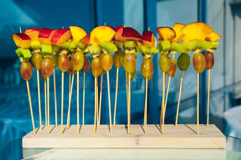 Owocowy jarski canape przy skewers z winogronami, kiwi i brzoskwinią przy czystym błękitnym tłem, catering przekąski usługa zdjęcia royalty free