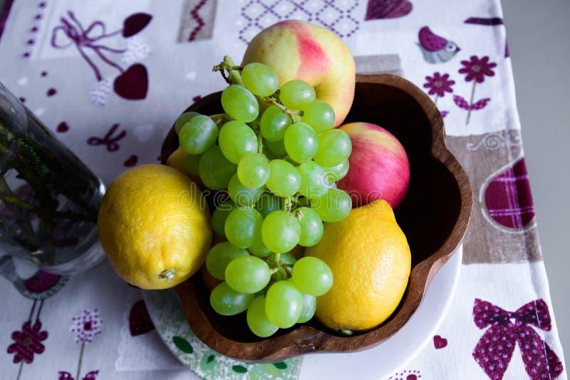 Owocowy kosz z jabłkami różne ilości, brzoskwinia i winogrona na białym tle, obraz royalty free