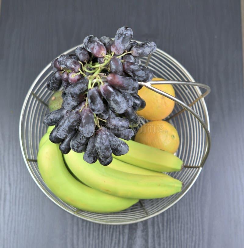 Owocowy kosz z winogronami na wierzchołku obraz stock