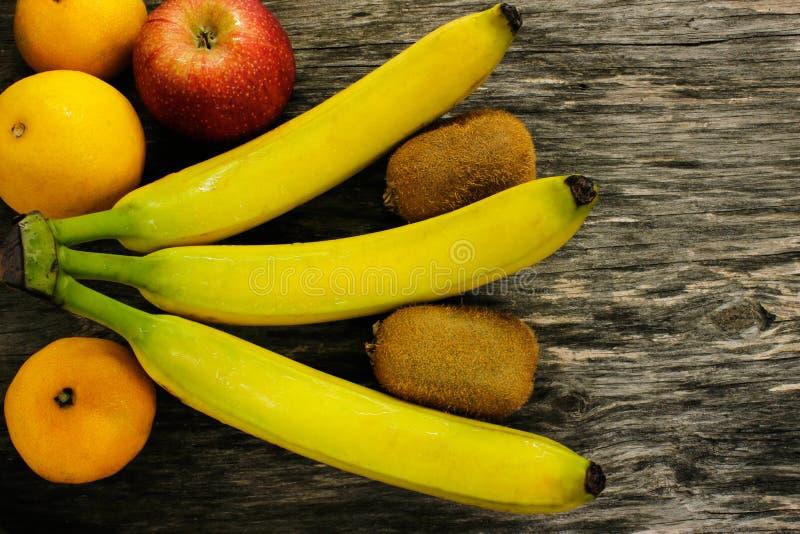 Owocowy półmisek świeże mandarynki, kiwi, czerwoni jabłka i banany na szarym drewnianym stole, zdjęcia stock