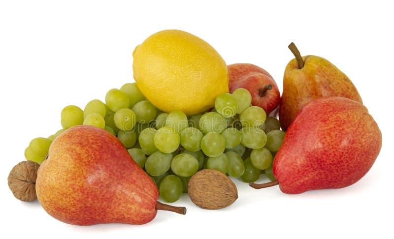 Owocowy p??misek dojrzali zieleni orzech?w w?oskich winogrona i czerwone aromatyczne bonkrety odizolowywaj?cy na bielu zdjęcie royalty free