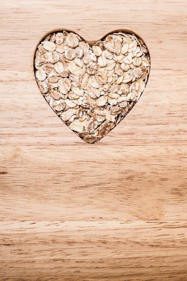 Owsa zboża serce kształtujący na drewnianej powierzchni obraz royalty free